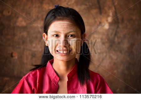 Young Myanmar female with Thanaka, a yellowish-white paste made from ground bark and used as a cosmetic and for sunburn protection.