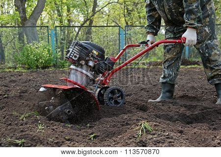 Man working in the garden preparing ground cultivator