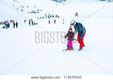 The child learning to ski and man on the slope in Bansko, Bulgaria