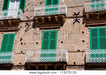 Old Italian stone house front with green shutter blinds and balcony in Tropea