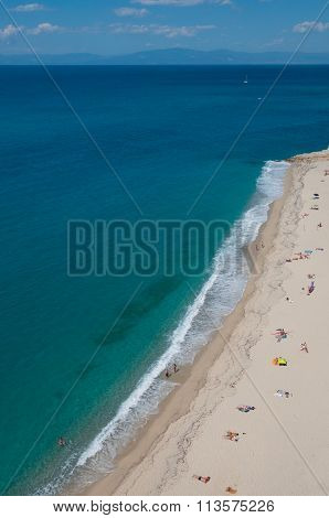 Yellow clean sand beach with people sunbathing next to mediterranean sea at coast of Tropea