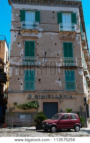 Italian stone house fron with green shutter blinds and smal red car in Tropea