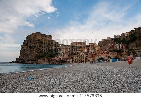 Stone beach and old small italian town on cliff under blue sky