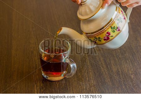 Old-style porcelain kettle pouring tea from jug to cup of tea