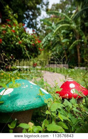 Two stone mushroom in the green grass of a garden