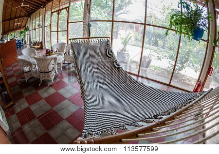 White huge hammock and rattan furniture on tiled floor in a hostel