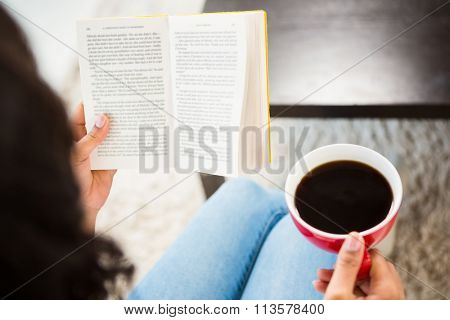 Cropped image of woman with coffee reading book in the living room