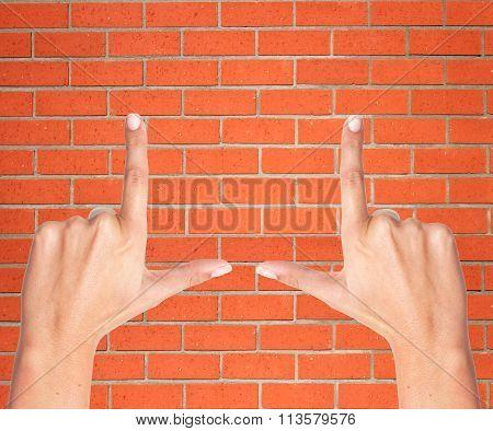 Finger Frame Over Orange Brick Wall