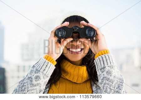 Smiling woman wearing winter clothes and looking into binoculars outside