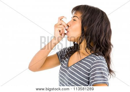 Casual woman using her inhaler against white background