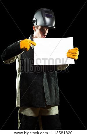 handsome welder holding a blank form. isolated on black background