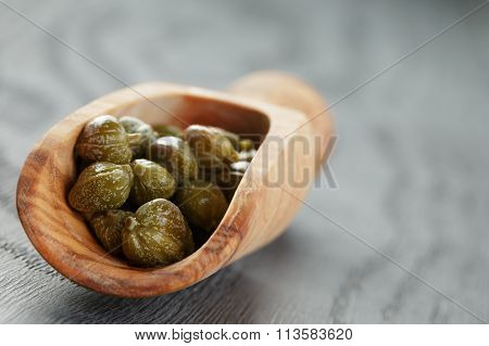 marinated capers in olive scoop on wood table
