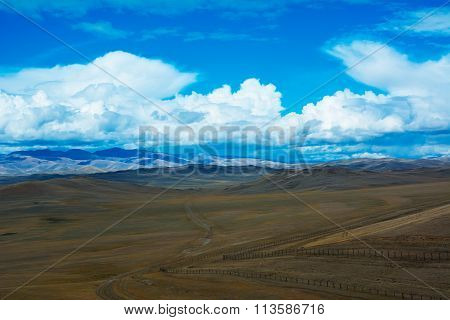 Steppe Landscape With A Road, Mountains, Blue Sky