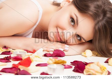 closeup woman on rose petals in white underwear