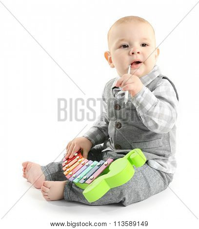 Adorable baby with plastic colourful xylophone isolated on white background
