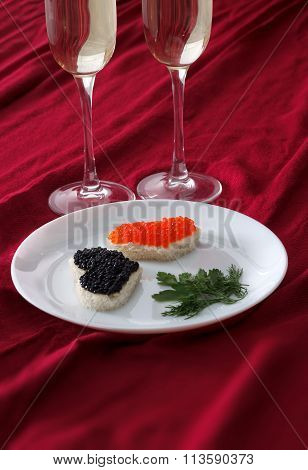 Heart Shaped Toasts With Red And Black Caviar And Two Glasses Of Champagne On White Plate On Red Dra
