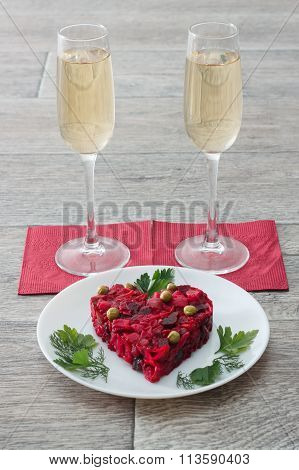 Beetroot And Vegetables Salad Made In Hearth Shape Served With Herbs On Plate With Two Glasses Of Ch