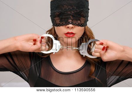 Sexual woman holding handcuffs.