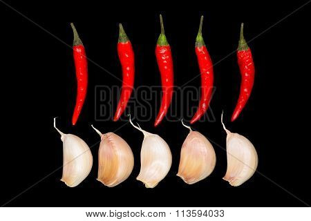 Red chili peppers and garlic on the black background