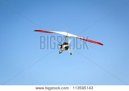 Motorized hang glider soaring in the blue sky