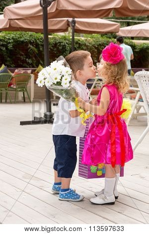 The Boy Kid Gives Flowers To Girl Child On Birthday. Little Adorable Girl Celebrating 3 Years Birthd