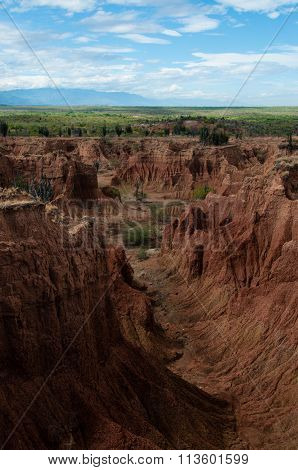 Steep cliff and valley of red orange sand stone rock formation in hot desert Tatacoa under blue sky,