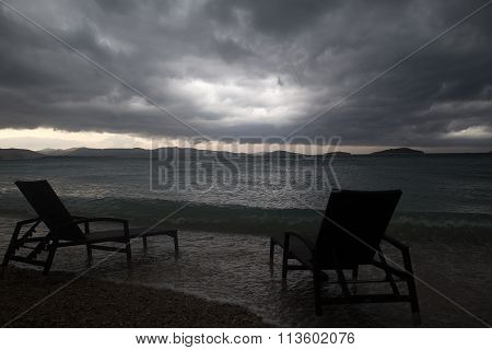Two Chaise Lounges On Beach