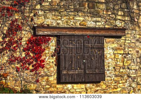 Closed Wooden Window on Stone Wall
