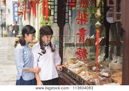 SHANGHAI, CHINESE PEOPLE'S REPUBLIC - CIRCA NOVEMBER 2015: Two chinese schoolgirls look at cakes in