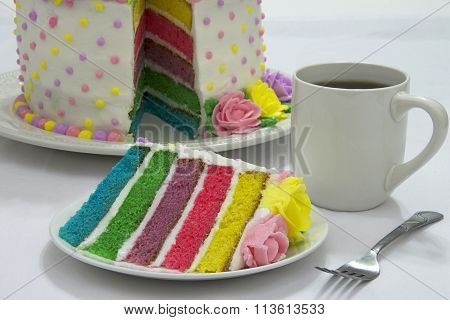 Slice of pastel rainbow rose dot cake on plate with coffee