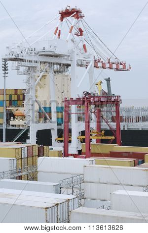 Large harbor crane loading containers on a a large cargo vessel