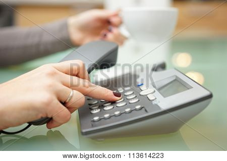 Woman Is Pressing Button On On The Phone Dial Pad And Drinking Coffee