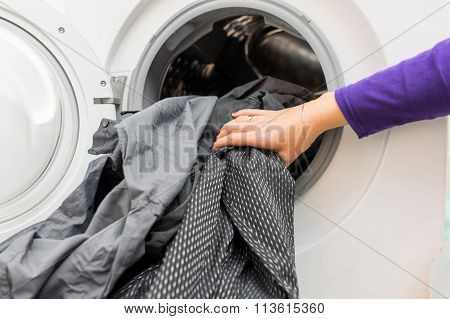 Female 's Hands Putting  Dirty Clothes Into Washing Machine