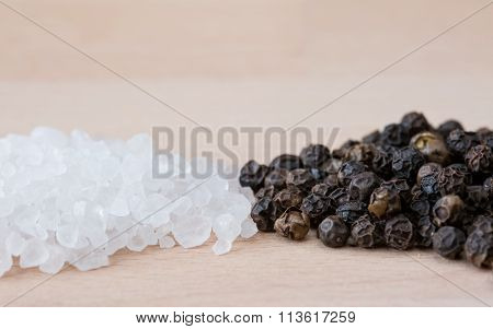 Heaps of rock salt and black peppercorns