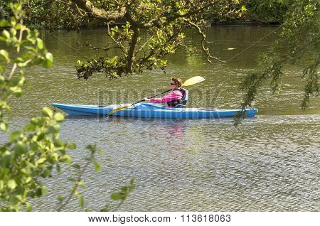 A woman canoeing along the river