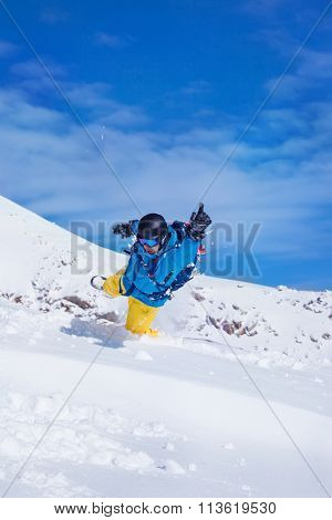Active male in snowboard outfit jumping in snow