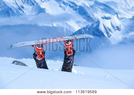 Legs of a snowboarder stuck in deep snow upside down