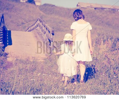 Mother and daughter walking on the meadow.