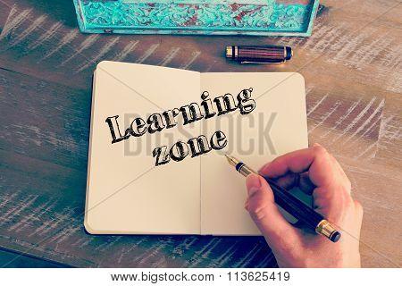 Motivational Message Learning Zone Written On Notebook
