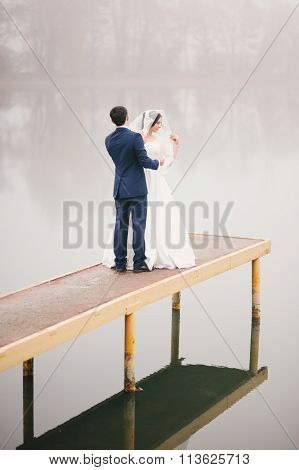 groom corrects  veil for  bride standing on  pier