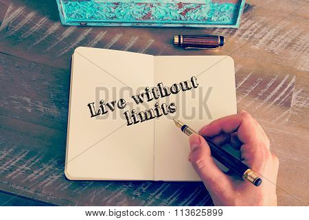 Motivational Message Live Without Limits Written On Notebook