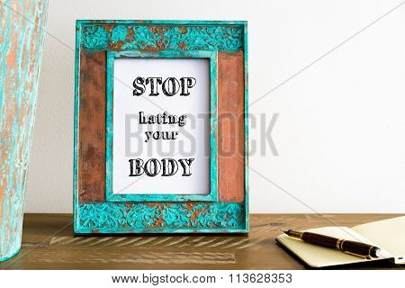 Vintage Photo Frame On Wooden Table With Text Stop Hating Your Body