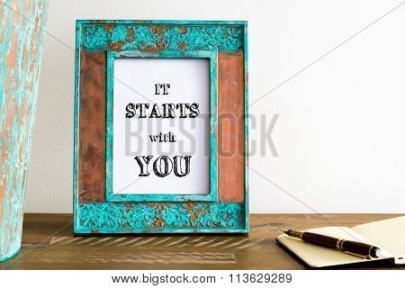 Vintage Photo Frame On Wooden Table With Text It Starts With You