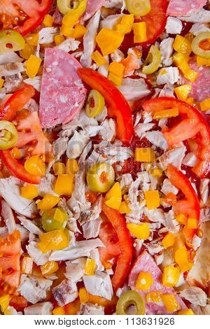 Closeup of raw pizza with vegetables and sausage