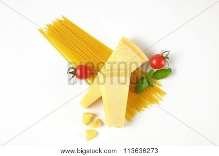 two wedges of fresh parmesan cheese, vegetables and spaghetti on white background