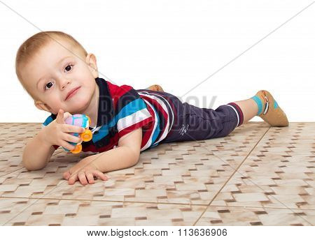 The Little Boy, Lying On A Floor, Plays With The Toy Car And Points A Finger At The Viewer