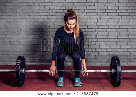 Female athlete doing deadlift at gym