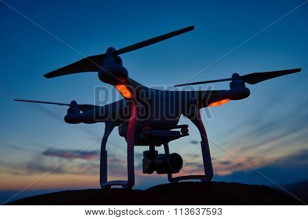 drone quadrocopter with digital camera at sunset