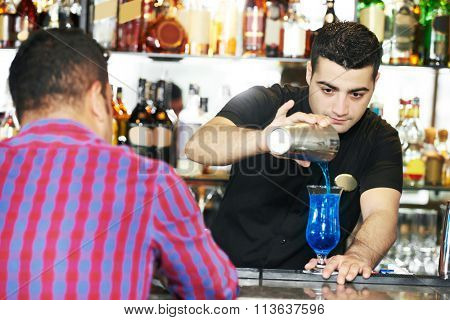 Barman worker serving cocktail in  bar
