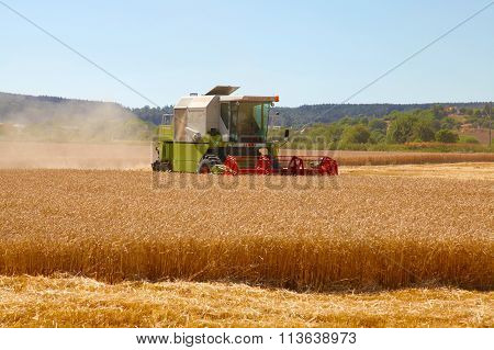 CZECH REPUBLIC, CHLUMCANY, 2 AUGUST, 2013:Combine harvester at the edge of grain field during hot ha